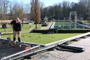 Sebastian Bock säubert die Solar-Anlage auf dem Dach des Rasteder Freibads.